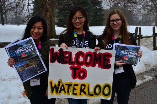 "Volunteers holding ""welcome to Waterloo"" signs."