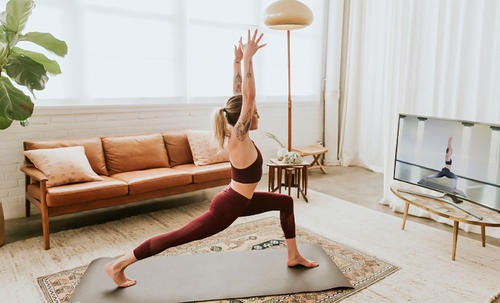 A woman does yoga in front of a television.