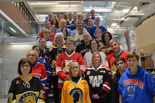 Members of the Faculty of Arts wearing jerseys stand together in the Hagey Hub.