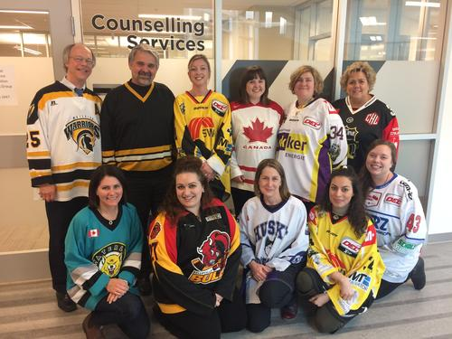 Members of Counselling Services wear sports jerseys outside their office.