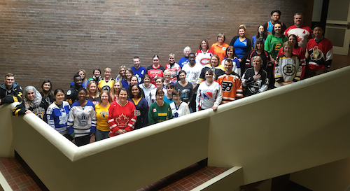 Members of the Registrar's Office wearing sports jerseys on the steps inside Needles Hall.