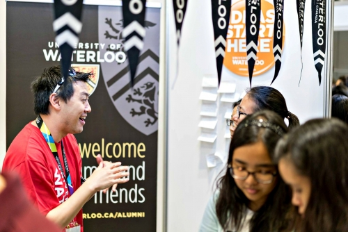 A volunteer welcomes visitors to a University of Waterloo booth.