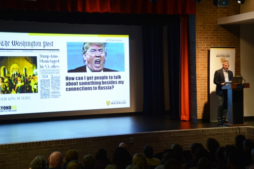 David DeVidi speaks next to a projected image of Donald Trump.