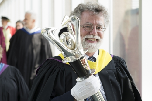 Mark Haslett carries the University's mace during last June's convocation ceremony.