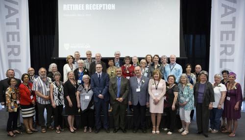 President Feridun Hamdullahpur and retirees stand for a group photo in Fed Hall.