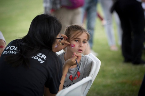 A Waterloo volunteer paints a child's face.