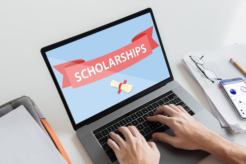"A laptop screen with the word ""scholarships"" on it."
