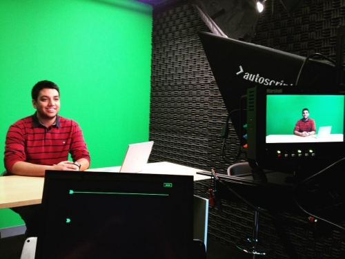 Chirag Sheth sitting in front of a green screen and a video camera.