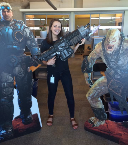 Tina Wilton poses with a prop rifle and Gears of War cutout figures.