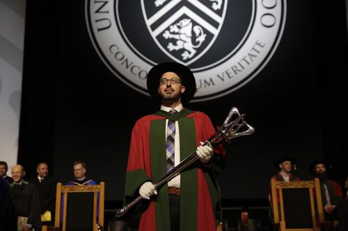 Chris Perlman hefts the University mace at Convocation.