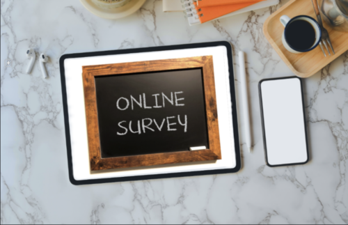 "A slate with the phrase ""Online Survey"" appears as an app on a tablet on a tabletop next to a smartphone."