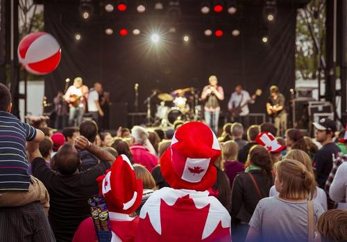 The crowd showing off their red and white gear at the main stage at the Canada Day celebration.