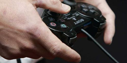 A person holds a PlayStation video game controller.