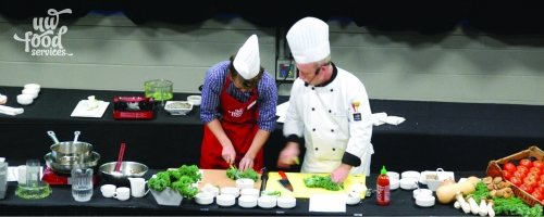 A Food Services cooking show event featuring a chef and assistant.