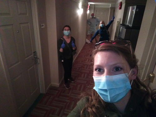 Hotel staff and volunteers in PPE gear in a hallway.