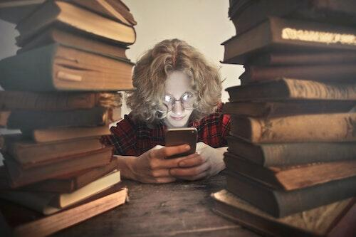 A young person reads a smartphone while surrounded by physical textbooks.