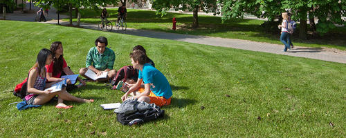 Students sit in a group on some campus green space.