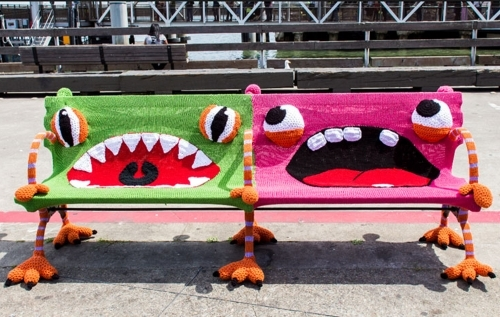 "A park bench ""yarn bombed"" to look like a pair of creatures."