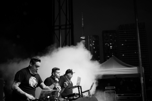 A Tribe Called Red performs with the CN Tower in the background.