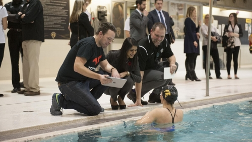 Swimming coach Jeff Slater (right) and MP Bardish Chagger speak with Warrior swim team member.