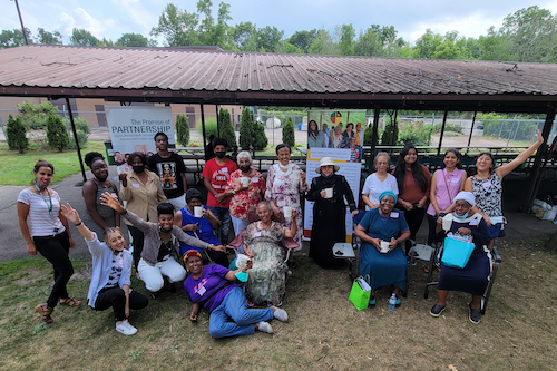 Staff, volunteers, and participants posing outside together for a photo during one of their summer community events.