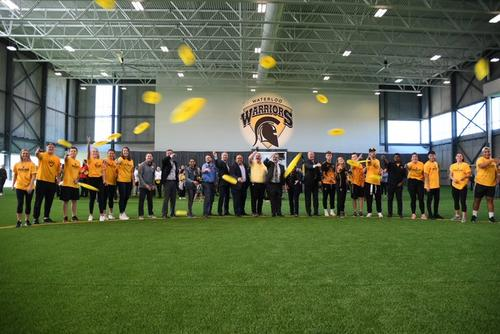 Group of Waterloo athletes and executives throwing yellow frisbees