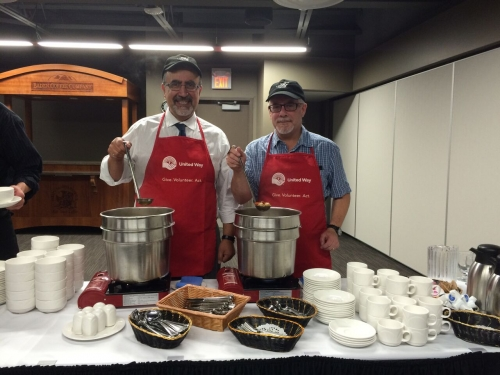 Feridun Hamdullahpur and Douglas Peers serve food.