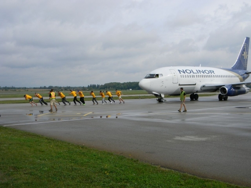 Waterloo volunteers pull a 737 jetliner across the tarmac.