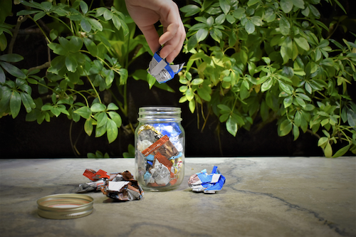 A person puts small bits of paper wrappers in a jar.