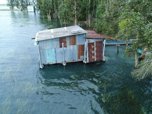 A small house designed to withstand flooding is shown on the water