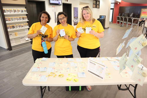 Three Thrive volunteers wearing yellow Thrive shirts at a sign-up table.