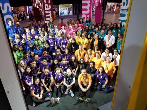 Recruitment officers and other volunteers in faculty colour-coded shirts at the University of Waterloo's booth.