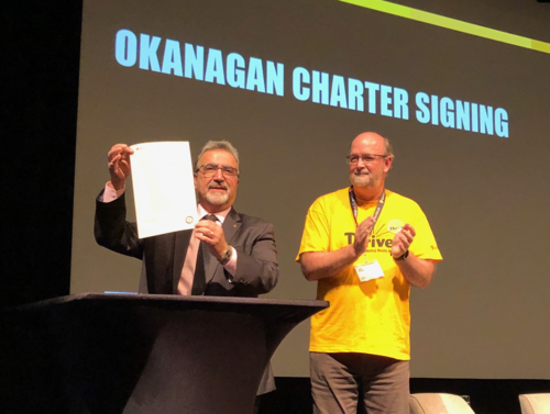 Feridun Hamdullahpur holds up a copy of the Okanagan Charter as Chair of the Student Mental Health Committee John Hirdes.
