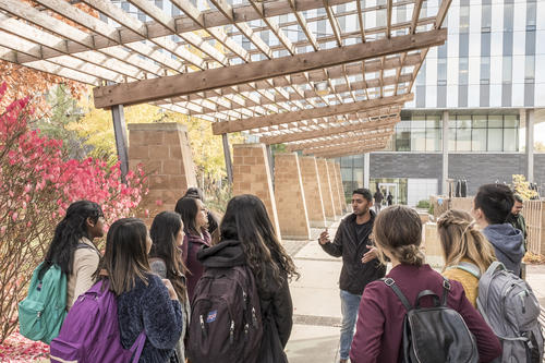 A volunteer conducts a campus tour in the shadow of the loggia outside the Student Life Centre.