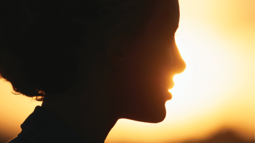 A woman's face silhouetted by the sun.
