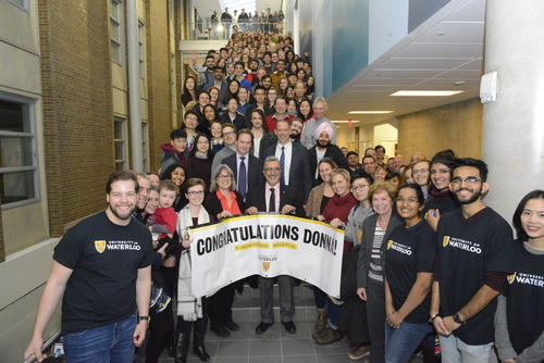 A crowd of well-wishers joins Feridun Hamdullahpur and Donna Strickland for a goup photo on the stairs of the Science Teaching Complex.