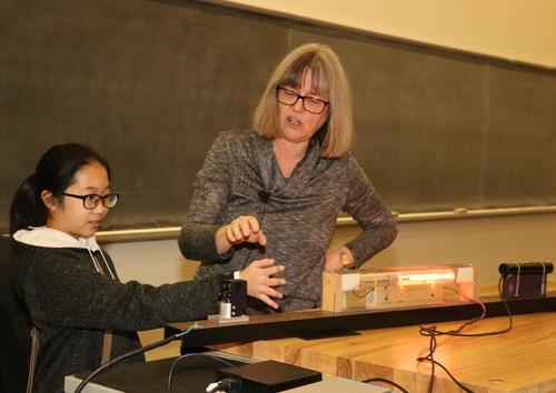 Professor Donna Strickland and a student volunteer demonstrate the power of a laser.