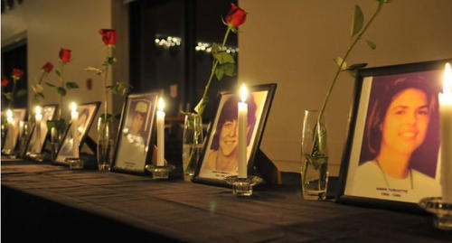 Photos of the victims of the December 6, 1989 shooting surrounded by roses and candles.