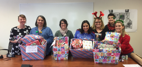 Staff from the Arts Undergraduate Office wrapping gifts for a sponsor family this Christmas.