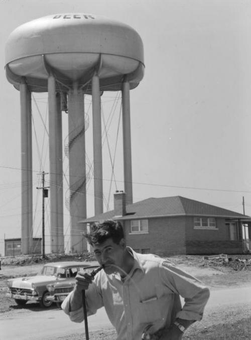 "A man drinks from a hose in front of the Lester Street Water Tower with the word ""BEER"" painted on it."