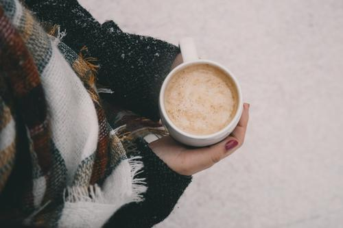 A woman in the snow holds a hot drink.
