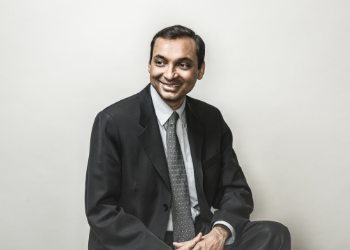 Sushanta Mitra in suit, smiling against blank wall