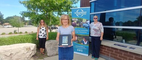 Three VAC volunteers stand outside, and one is holding a piece of artwork.