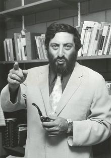 Professor Joseph Gold stands with a pipe in hand in his office circa 1975.