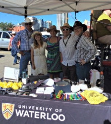 Volunteers in cowboy getups staff a University of Waterloo alumni booth.