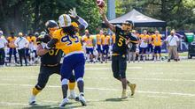 Tre Ford throws a football during a game against Laurier.