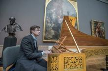 Christopher Bagan sits in front of a harpsichord.