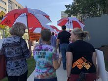 VAC volunteers walking with umbrellas.