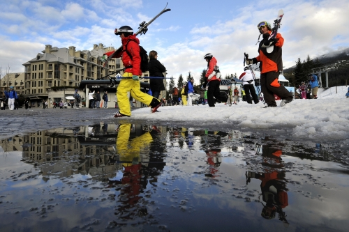 Skiiers carry their skis over a puddle in Whistler, BC.