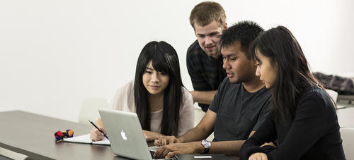 A group of students working on a laptop